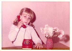 Liane als Kind mit enem roten Spielzeugtelefon